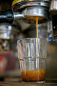 Close-up of espresso dripping from a bottomless portafilter into glass cup