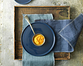 Overhead View of Tumeric Spice in Antique Spoon on Blue Plate