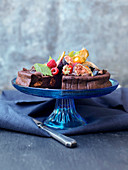 Schokoladenkuchen mit Früchte-Topping auf Tortenständer