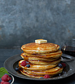 Pancake-Stapel mit Butter, Beeren und tropfendem Sirup