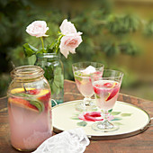 Jar of pink lemonade with basil, peaches and raspberries with two glasses, a tray and jar of roses on table outside