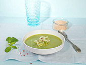 Bowl of green pea soup with garnish of pea shoots, shaved fennel and pink peppercorns and sea salt