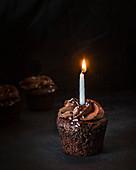 Schokoladencupcake mit kleiner Kerze