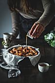 Pouring caramel on cinnamon rolls