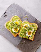 An open avocado sandwich with egg and herbs