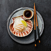 Scallop sashimi on shell with daikon, lime and soy sauce