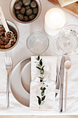 Place setting decorated with twig on table with white tablecloth