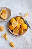 Meyer-Zitronen, ganz und geschnitten in Schalen
