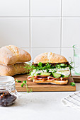 Italian ciabatta with ham, cucumber, brie, baby pea greens and and caramelized onion jam