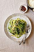 Creamy pesto pasta with crushed red pepper and Parmesan cheese