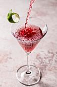 Granatapfel-Cosmopolitan Cocktail wird in ein Martini-Glas gegossen