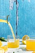 Orangensaft in Glas eingießen