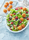 Salad with fried cheese balls and raspberries