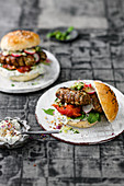 Lamb kebab burger with grilled tomatoes and an onion and herb mix