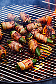 Stuffed jalapeños wrapped in bacon on a grill