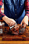 Tear a pork shoulder with two forks or pulled pork claws