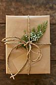 Geschenkverpackung aus Packpapier, Schnur, Geschenkanhänger und Wacholderzweig