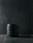 Pile of deep grey plates on black stone background