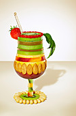 Cocktail glass composition with sliced fruit and nuts