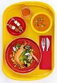 Yellow tray Spanish theme with gazpacho, shrimp paella, and cheese skewers