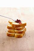 Ein Löffel mit roter Marmelade auf Stapel Brioche-Scheibenn
