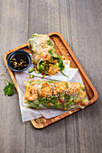 Asian summer rolls with salad, salmon filling and sesame