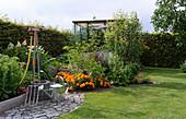 Wasserstelle im Schrebergarten, Gießkanne und Grabgabel, Blick auf Blumenbeet und Gewächshaus