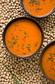 Roast tomato and red pepper soup on background of dried chickpeas