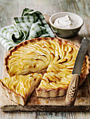 Apple Tart on a board with whipped cream and knife