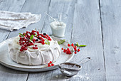 Meringue cake with whipped cream and red currant