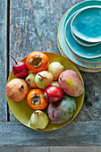 Fruit arrangment tamarillos, mangoes, khaki, pears, pomegranate and colored plates on outdoor table