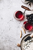 Glasses of red wine, cheese and grapes on rustic background
