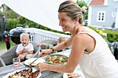Frau serviert das Essen auf der Terrasse