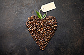Coffee beans in shape of heart on rustic background