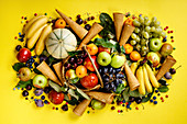 Fresh fruits, berries and ice cream cones on yellow background
