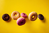 Various decorated doughnuts falling on yellow background