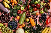 Bio-Früchte, Beeren und Smoothies auf rosa Untergrund
