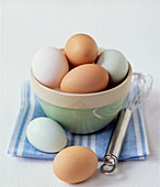 selection of different coloured organic eggs in a bowl with whisk