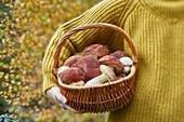 Woman holding basket with porcini mushrooms