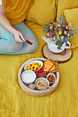 Tray with ingredients for detox breakfast, woman holding raspberries stick