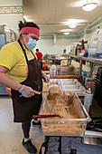 Volunteer making bread, Detroit, Michigan, USA