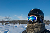 Tourist wearing a helmet for snowmobile driving, Sweden