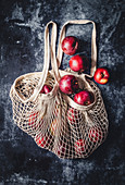 Cotton net bag with apples on dark background