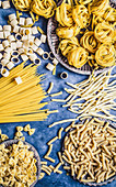 Dry pasta in different shapes on a blue background