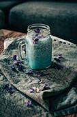 Smoothie with violet flowers in jar