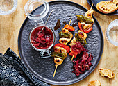 Grilled poultry and vegetable skewers with red onion chutney