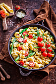 Pasta in cheese sauce with cherry tomatoes and sugar peas