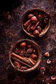 Brown spices and nuts in coconut shells
