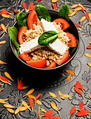 Bowl with couscous, feta, spinach and tomatoes