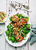 Quinoa and salmon trout patties with cucumber and radish salsa and salad